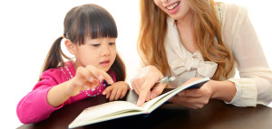 Little girl studying in English with teacher ** Note: Shallow depth of field